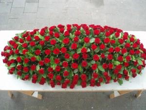 Kistbedekkend grafstuk met rode rozen